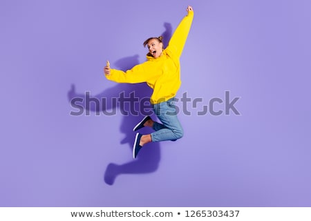 Full length portrait of an excited girl wearing hoodie jumping Stock photo © deandrobot