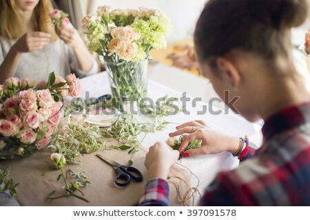 Happy florist woman working with flowers in workshop. Stock photo © deandrobot