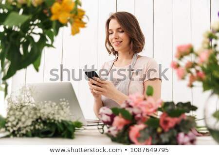 Cute cheerful florist lady using laptop computer chatting by mobile phone. Stock photo © deandrobot