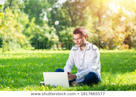 image of caucasian handsome man in casual wear sitting on grass stock photo © deandrobot