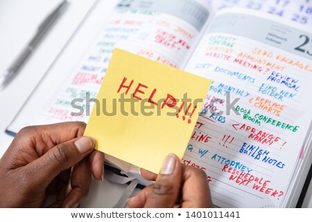 Human Hand Holding Adhesive Note With Help Text Stock photo © AndreyPopov