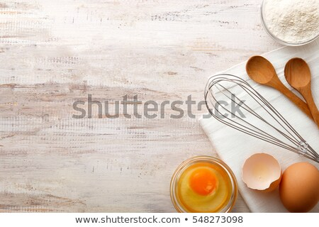 Eggs, wooden spoon and whisker. Kitchen utensil for cake, pastry Stock photo © marylooo