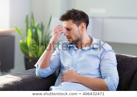 Foto stock: Man Having Stomach Pain Sitting On Sofa