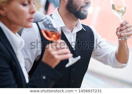 Bearded sommelier with glass of white wine checking its quality Stock photo © pressmaster