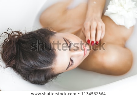 Young woman in bath with milk and flowers  Stock photo © dashapetrenko