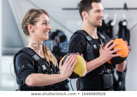 Fit woman and man with ball in wireless ems exercise gym Stock photo © Kzenon