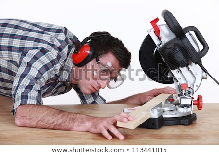 Man positioning a plank of wood in a mitre saw Stock photo © photography33