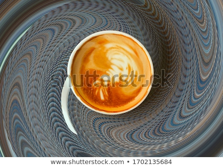 Delicious latte in glass with coffee art swirl design. Stock photo © ElinaManninen