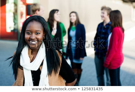 Happy african american college student with laptop standing on w Stock photo © vlad_star