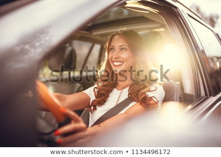 smiling woman driving a car at sunset stock photo © vlad_star