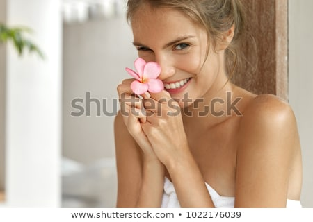 Cheerful cute young beautiful woman in bathroom take care of her skin doing makeup. Stock photo © deandrobot