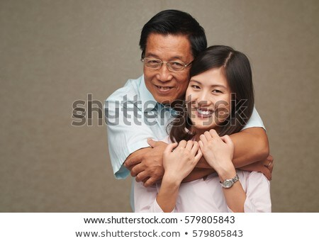 Happy mature man and his young daughter embracing and looking at each other Stock photo © pressmaster