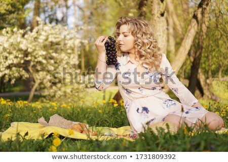 Woman eating a bunch of grapes by the sea Stock photo © photography33