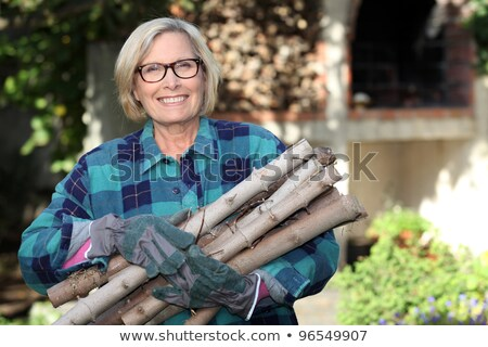 senior woman gathering wood in the garden Stock photo © photography33