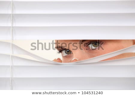 woman peering through blinds stock photo © photography33