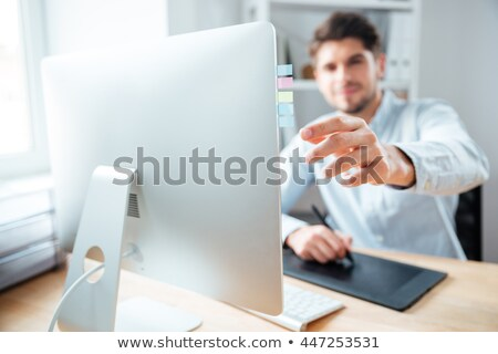 man designer putting stickers on monitor of comuter in office stock photo © deandrobot