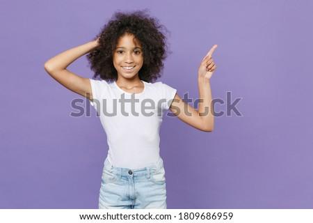 Little african schoolgirl pointing forefinger up. Stock photo © RAStudio