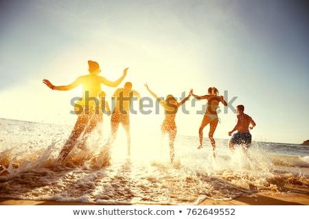 Cuatro personas ejecutando agua sonriendo riendo surfista Foto stock © IS2