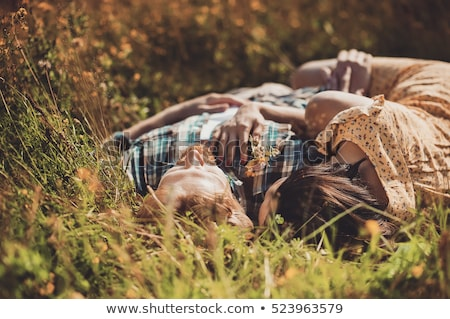 Couple lying at the beach and kissing at sunrise. stock photo © Massonforstock
