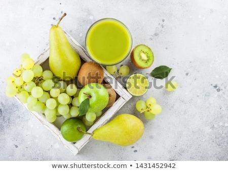 Fresh raw organic green toned fruit in white vintage box on ston Stock photo © DenisMArt