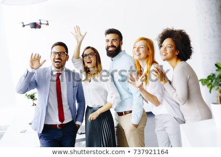 Young happy business people letting the drone camera to fly over Stock photo © boggy