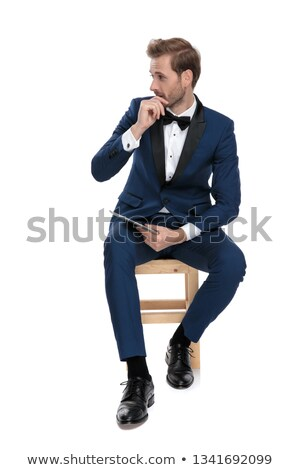 astonished guy looks away holding a notepad in his hand  Stock photo © feedough