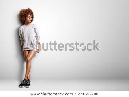 Blonde woman with curly beautiful hair smiling on gray background. Stock photo © studiolucky