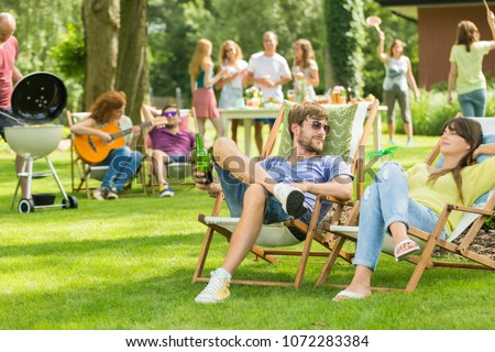 friends playing guitar and chilling at summer park stock photo © dolgachov