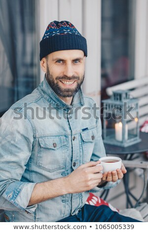 Happy delightful middle aged male with beard and mustache, wears warm jacket and hat, holds artifici Stock photo © vkstudio