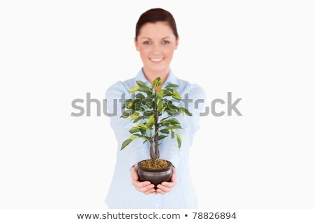 Attractive red-haired woman holding a houseplant while standing on a white background Stock photo © wavebreak_media