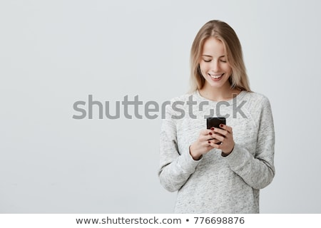 pretty young woman chatting by her phone stock photo © deandrobot
