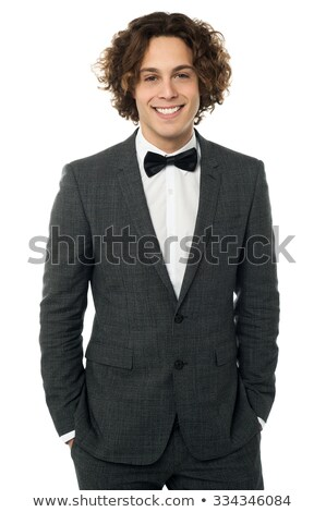 cool elegant man wearing tuxedo posing with hands in pockets stock photo © feedough