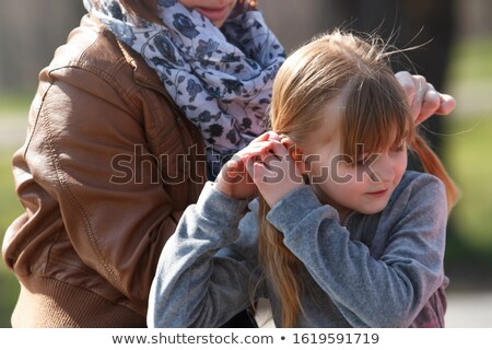 Pretty mother is curling her daughters hair Stock photo © dashapetrenko