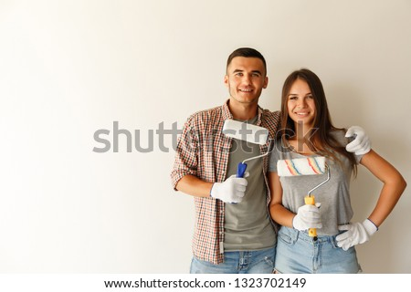 Image of young couple man and woman painting white wall and maki Stock photo © deandrobot