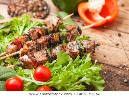 Grilled pork and chicken kebab with paprika in round wooden plate of lettuce salad on wooden backgro Stock photo © DenisMArt