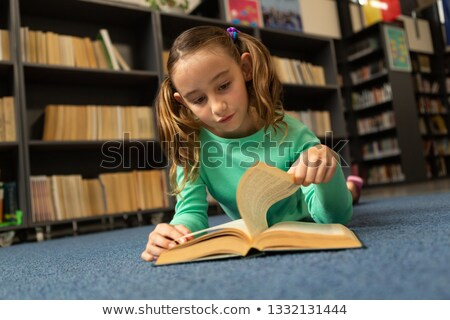 Front view of Caucasian schoolgirl lying on floor and turning a page in a book in library at element Stock photo © wavebreak_media