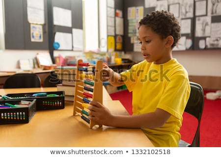 Side view of focused mixed-race schoolboy learning mathematics with abacus in a classroom at element Stock photo © wavebreak_media