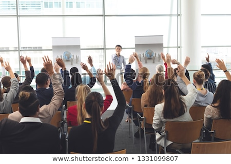 Rear view of diverse business people raising hands while an Asian businessman is speaking at busines Stock photo © wavebreak_media