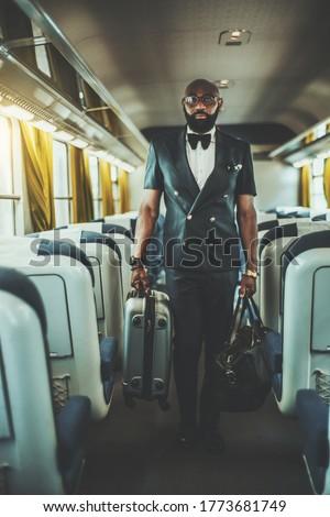 Bald male business traveler in suit and eyeglasses standing by elevator door Stock photo © pressmaster