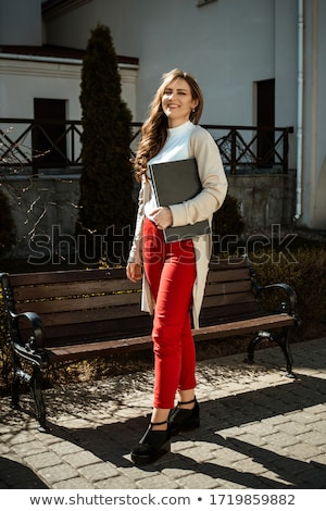 A young girl is standing in the street with a laptop in her hands. On the girl put on sunglasses. Stock photo © ElenaBatkova