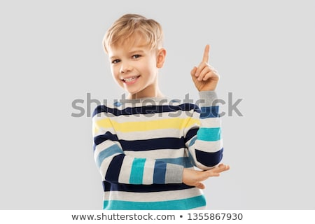 little boy in striped pullover pointing finger up Stock photo © dolgachov