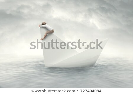 White paper boat is sinking in the sea water Stock photo © cherezoff