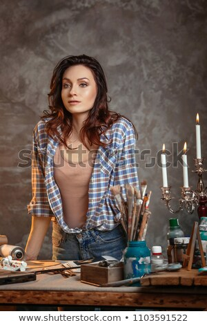 Modern woman painter looking at her drawings in art class Stock photo © deandrobot