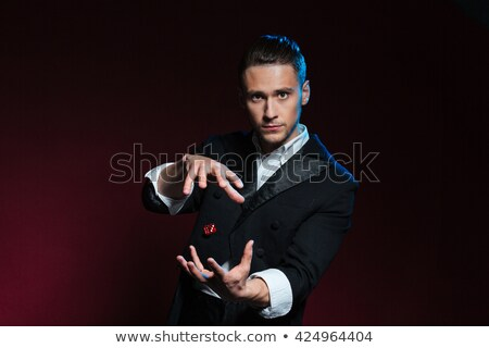 confident young man magician showing tricks using one flying dice stock photo © deandrobot