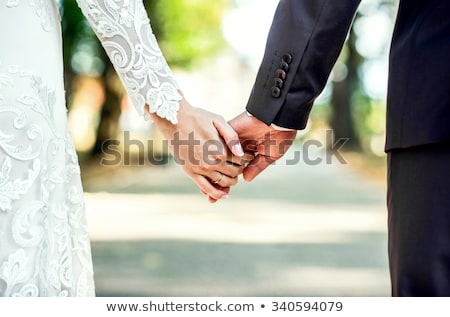Stock photo: Young bride and groom holding hands together