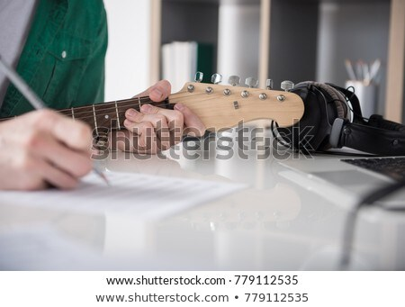 man with guitar, pencil and paper at music studio Stock photo © dolgachov