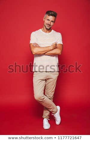 Full length photo of brunette man in striped t-shirt smiling and Stock photo © deandrobot
