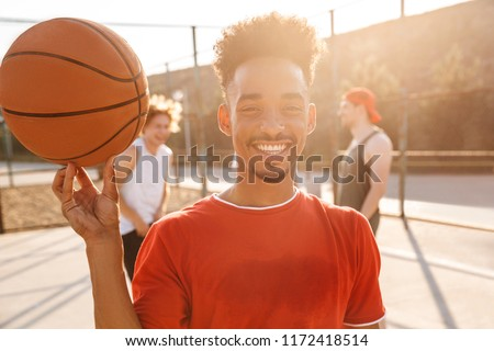 Image of sporty young boy spinning ball on his finger, while pla Stock photo © deandrobot