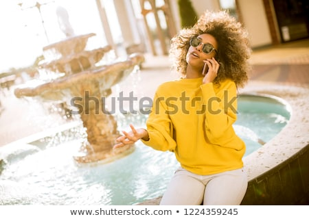 Aftican american young woman sits near fountain and talks on mob Stock photo © boggy