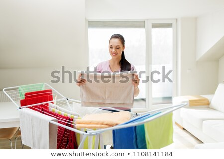 woman taking bath towels from drying rack at home Stock photo © dolgachov